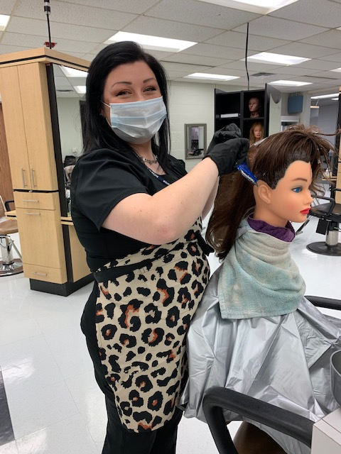 Cosmotology student Brooke McCune practices hair coloring techniques on a manniquin